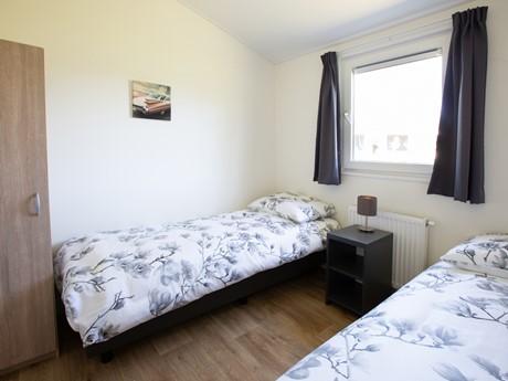 Tweepersoons slaapkamer met kast in waterbungalow Vakantiepark Molenvelden